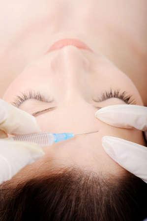 high angle shot: Botox injection to the female forehead - high angle shot