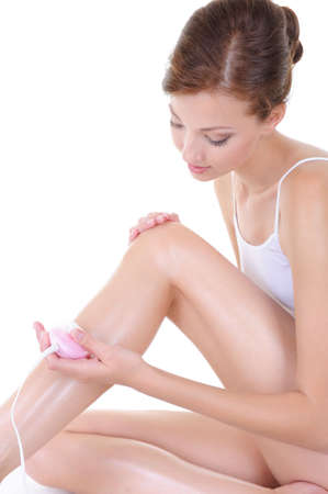 beautiful young woman shaving her legs with shaver - body care photo