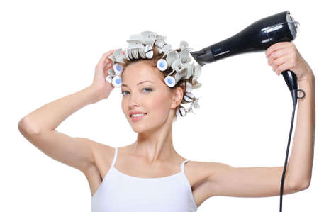hairdryer: happy beautiful young woman drying her head in hair-curlers Stock Photo