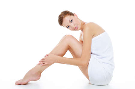 Female with beautiful legs sitting on the floor in white towel photo