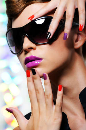 feminity: Face of young woman with multicolored manicure and fashion stylish sunglasses - colored background