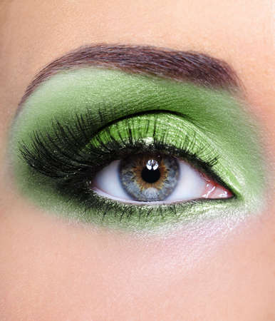 Green fashion make-up of woman eye - macro shot photo