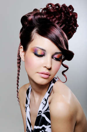 Pretty young woman with fashion creative hairstyle and bright multicolored eyeshadow photo