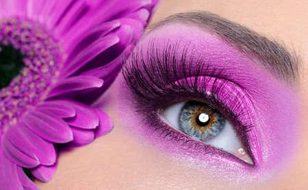 falso: Una mujer con el ojo morado de maquillaje y unas pesta�as largas y falsas - flor Gerber