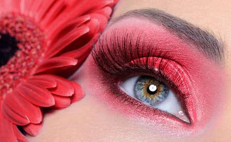 fashion woman eye with red make-up and long false eyelashes -  flower at background photo