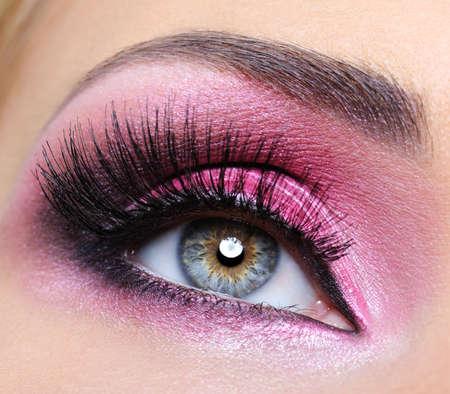 明るい深紅色のメイクアップと長いまつげと女性の目