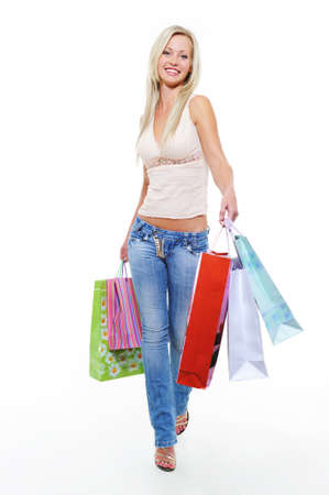 Young woman with purchases walking after shopping over white background Stock Photo - 5594172