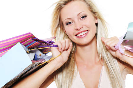 Close-up portrait of a blond happy woman with purchases - over white background photo