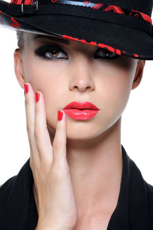 feminity: Close-up face of beautiful woman with bright red lips and fingernails in the fashion hat
