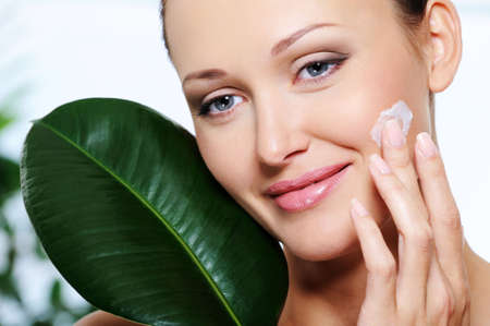 Beautiful smiling woman applying  moisturizer cream with a green fresh leaf at her face