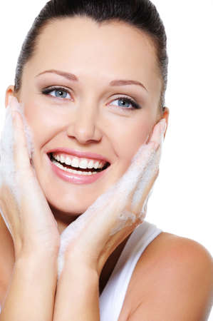 spume: Portrait of laughing happy beautiful woman cleaning her face Stock Photo