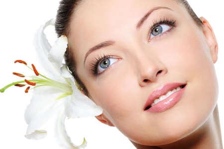 La piel sana de los jóvenes se enfrentan a la mujer hermosa con una flor en el pelo