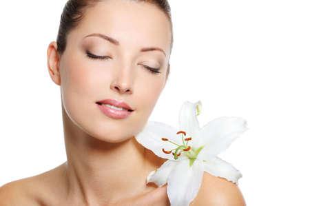 salud sexual: El rostro sereno de una fresca belleza de la mujer con los ojos cerrados y Flowe en el hombro
