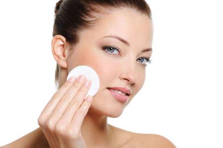 mujer limpiando: Hermosa mujer limpieza de su cara bonita con un bastoncillo de algod�n - sobre fondo blanco