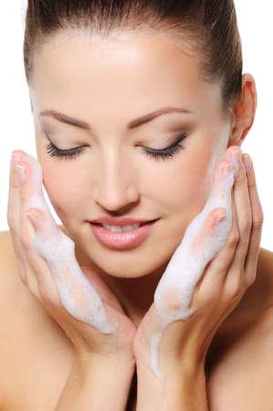 lavandose las manos: Hermosa mujer lavando la cara con espuma en la heands Foto de archivo