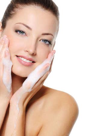 lavare le mani: Bella donna caucasiian lavarsi la faccia della salute bellezza con la schiuma sulle mani Archivio Fotografico