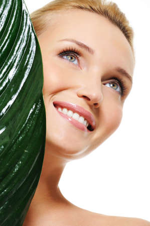 Close-up healthy face of a young beautiful happy laughing woman - green plant over background Stock Photo - 5627371