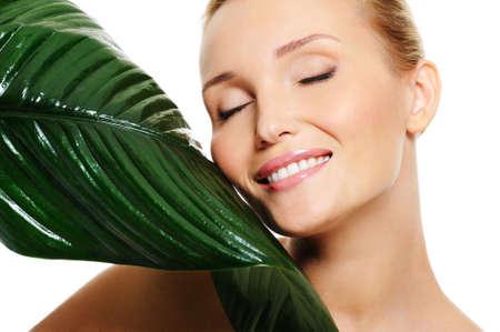 closed eyes: Mooie lachende vrouw met gesloten ogen te raken door haar wang een grote groene blad Stockfoto