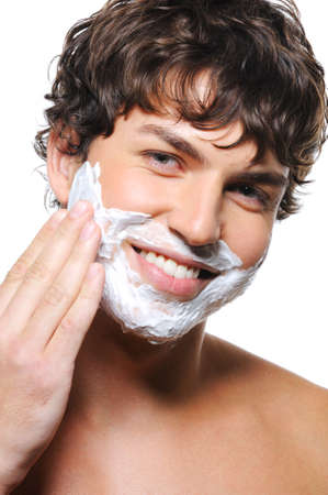 Close-up portrait of young happy mans face with shaving cream photo