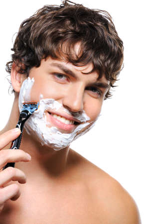 Happy laughing man shaving his face over white background photo