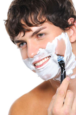 Portrait of handsome man shaving his face over isolated on white photo