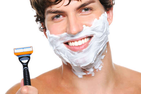 razor: Laughing mans face with shaving cream on it and razor near the face Stock Photo
