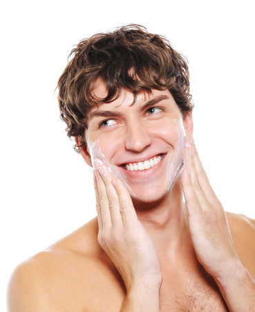 shaving cream: Man with happy smile applying moisturizing lotion after shaving for his face