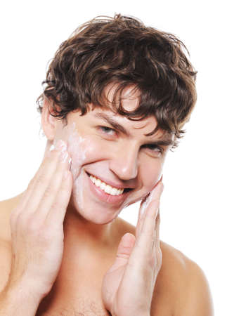 enjoymant: Happy man after shaving applying moisturizing cream upon his face
