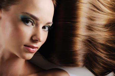 lussureggiante: Close-up bellissimo volto femminile con i capelli castani come sfondo