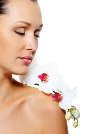 Portrait of beautiful woman in profile with a white orchid flower on her shoulder over white background Stock Photo - 5654704