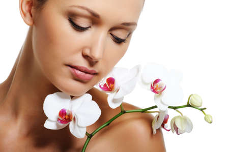 Face of pretty beautiful woman with a white orchid on her shoulder photo