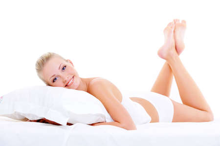 Beautiful nice woman in white lingerie lying down on the white pillow  photo