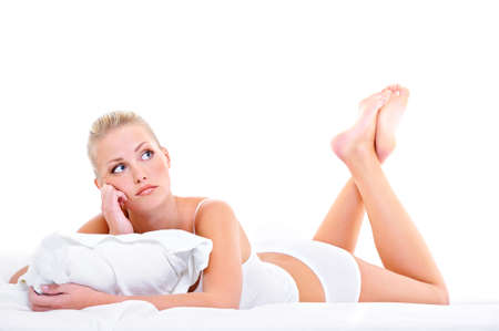 bored woman: Young bored woman with lying down ot he bed over white background Stock Photo