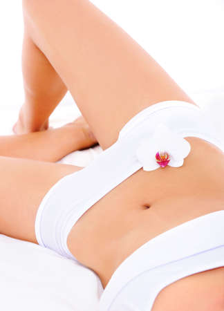 Fragment of perfect unblemished slim womans body in white lingerie photo