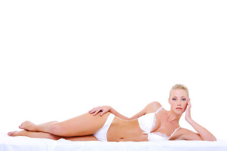 Beautiful caucasian blonde woman with perfect sexy body lying down on the bed Stock Photo