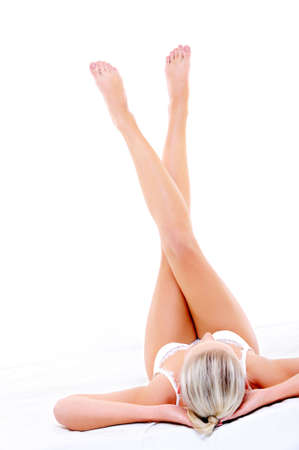 cross leg: Beautiful slim long woman legs directed up over white background