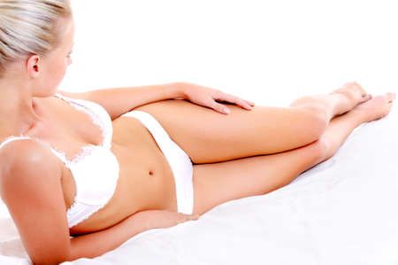 Beautiful slim legs and perfect woman body lying on the white bed  photo