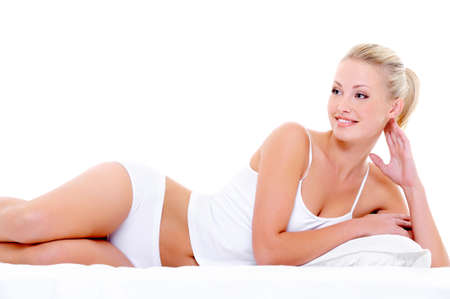 Happy beautiful smiling woman with a sexy body  lying in underwear on the white bed photo