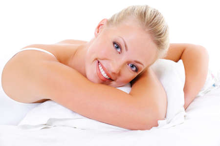 Happy beauty woman with toothy smile and healthy skin lying on bed and embrace pillow photo