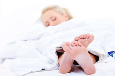 Feet of sleeping woman close-up protruding from under the bedspread photo