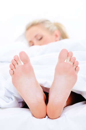 bed feet: Sleeping woman with a clean  feets protruding from under the bedspread