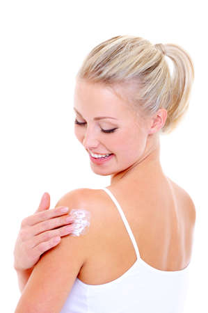 Happy woman caring about her shoulder applying cosmetic cream- isolated on white photo