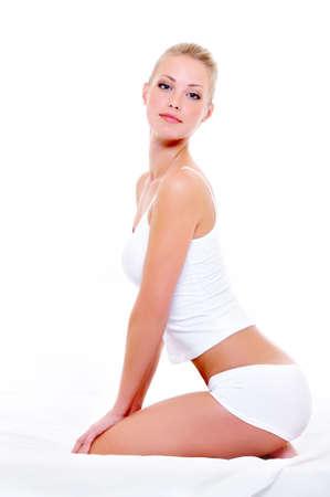 vrouw ondergoed: Portret van mooie vrouw met een sexy lichaam in ondergoed zittend op het bed