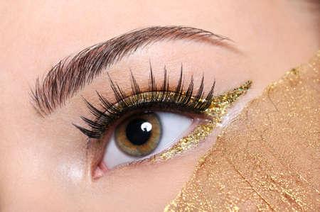 pesta�as postizas: Macro foto de una mujer con un ojo pesta�as postizas y el amarillo, de oro de maquillaje Foto de archivo