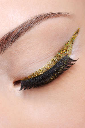 Closed eye of female eye with bright shining golden eyeliner arrow photo