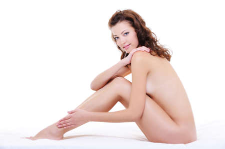 Beautiful caucasian woman with a perfect nude body sitting on the white bed photo