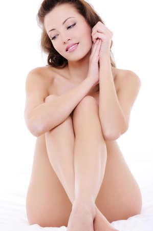 mujer desnuda sentada: Hermosa mujer desnuda elegante sentado en la cama con las manos en la cara