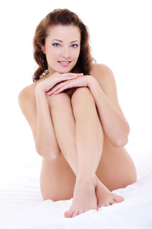 nude woman sitting: Beautiful happy smiling woman with a perfect nude lon legs sitting on bed