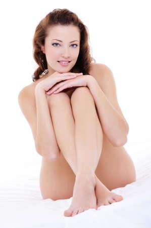mujer desnuda sentada: Hermosa mujer sonriendo feliz con un perfecto piernas lon desnudo sentado en la cama