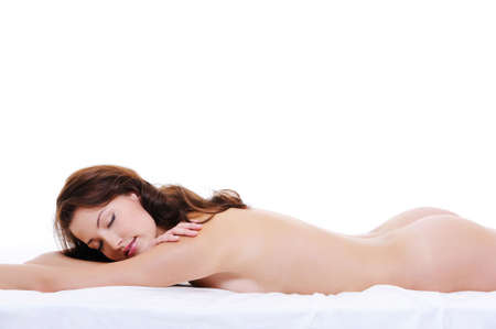 Young naked body of a cute serene woman lying down on bed with closed eyes